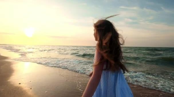 Slow Motion: Dívka běží v mělké vodě při západu slunce. Dívka v bílých šatech je spuštěn na okraj vody nedaleko moře. Jsem spokojený s mořem a na pláž. Využijte svobodu.