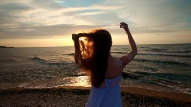 Női láb természetjáró turisztikai mezítláb partján naplementében. Lába alatt napkelte óceán parton haladó fiatal nő. A lány nedves homok a partvonal lépve. Lassú mozgás