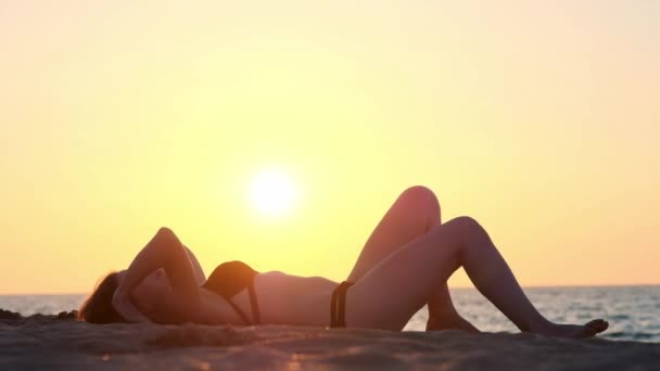 Young woman in bodysuit practicing yoga on the beach above sea at amazing sunrise. Fitness, sport, yoga and healthy lifestyle concept. Girl doing a bridge, Slow motion.