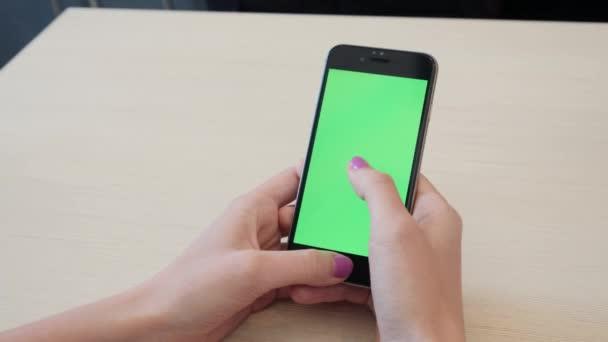 Schönes Mädchen mit einem Smartphone in den Händen von einem Greenscreen grünen Bildschirm, von Menschenhand halten mobile Smartphone mit Chroma-Key-green-Screen auf weißem Hintergrund, neue Technologie-Konzept