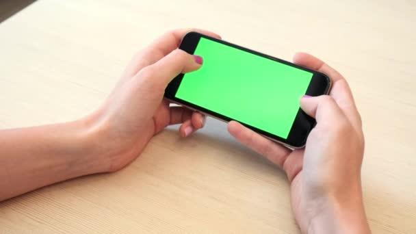 Krásná dívka držící smartphone v rukou zelená obrazovka zelené obrazovky, rukou člověka drží mobilní chytrý telefon s chroma key zelená obrazovka na bílém pozadí, nový koncept technologie