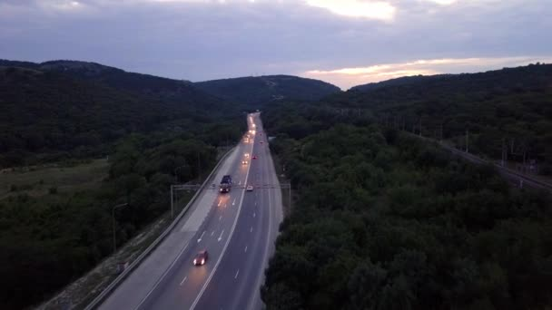 Aerial: road highway at sunset. Rides a lot of cars, headlights are included. Near mountains and forest.