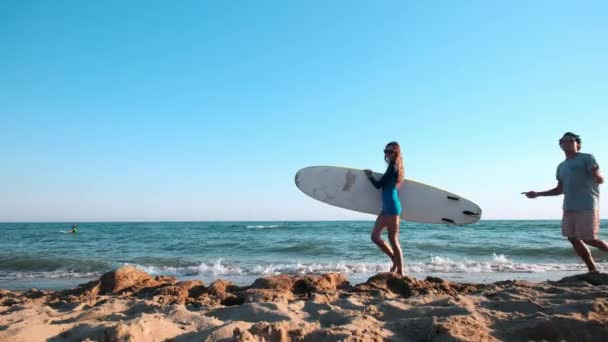Beautiful slim girl walking on the beach, holding surfboard. Behind her funny guy is walking. Running in the evening during sunset. A funny video.