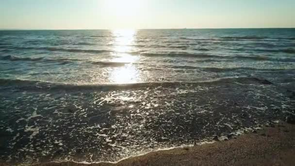 Letecká dron záběry vln směrem k skalnaté pobřeží na pláži. Dron létá od horských útesu směrem k moři. Malebný pohled krajina proti zamračená obloha při západu slunce.