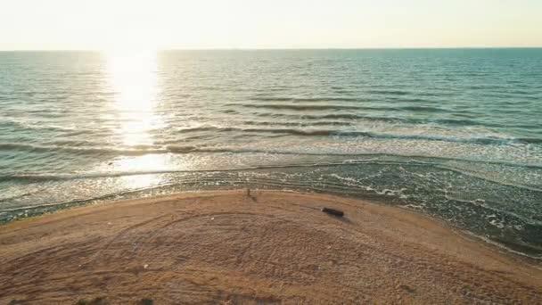 Letecká dron záběry vln směrem k skalnaté pobřeží na pláži. Dron létá od horských útesu směrem k moři. Malebný pohled krajina proti zamračená obloha při západu slunce