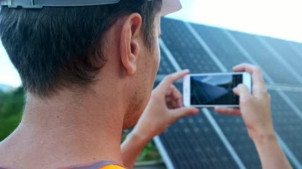 Inženýr expert v solárních fotovoltaických panelů s dálkovým ovládáním provádí rutinní akce pro systém monitorování pomocí čisté, obnovitelné zdroje energie. Je fotografie solárních panelů na smartphone