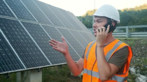 Inženýr expert v solárních fotovoltaických panelů s dálkovým ovládáním provádí rutinní akce pro systém monitorování pomocí čisté, obnovitelné zdroje energie. mluvil po telefonu
