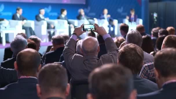 ein alter Geschäftsmann oder Politiker hört ein Seminar oder einen Vortrag über die wirtschaftliche Situation. macht Fotos oder dreht Videos mit dem Smartphone.