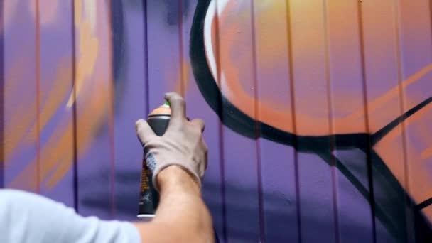 Mladý muž se plechovka barvy nakreslí graffiti na zdi. Jednou rukou detail.