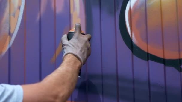 Egy fiatal srác a can of festék felhívja a graffiti a falon. Egyrészt közelről.