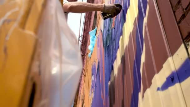 Alacsony nézet: egy fiatal férfi előadó felhívja a can of festék graffiti a falon. Kell tenni a torony építése. Egy ember foglalkozik a művészetben