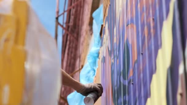 Alacsony nézet: egy fiatal férfi előadó felhívja a can of festék graffiti a falon. Kell tenni a torony építése. Egy ember foglalkozik a művészetben.