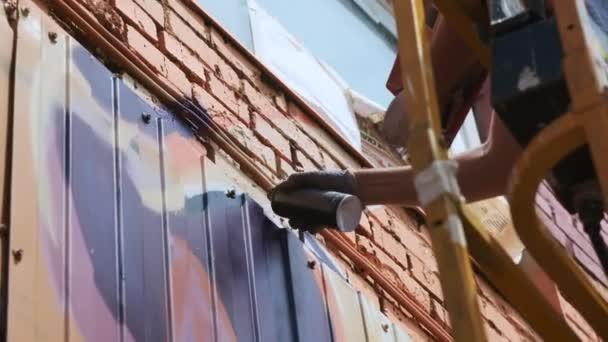 Nízkou pohled: mladý muž umělec nakreslí mohou malovat graffiti na zdi. Mělo by být na výstavbu věže. Muž v umění.