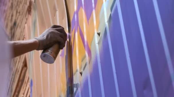 Mladý muž se plechovka barvy nakreslí graffiti na zdi. Jednou rukou detail