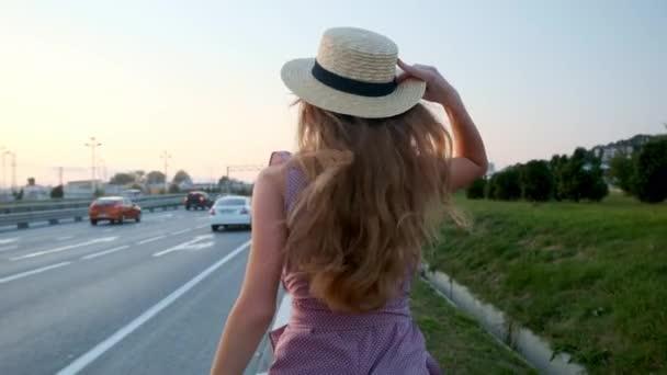 Mädchen geht mit Koffer auf die Straße. in der Nähe der Autobahn und viele Autos..