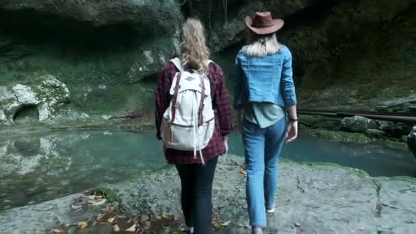 Two young Caucasian female travelers travel along a tropical cave. On back marching backpack. Inspired by the beauty of nature. Looking for adventure in exotic places of planet. Active lifestyle.