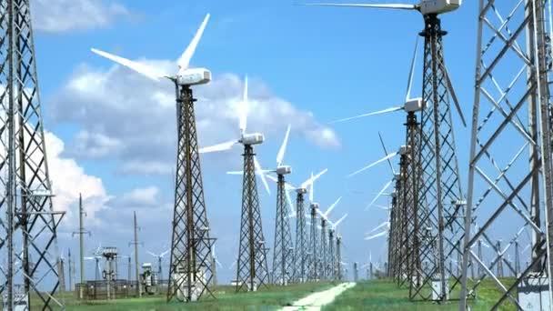 Staré větrné generátory v poušti na zelené trávě, proti modré obloze