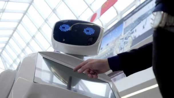 Kibernetikus rendszer ma. Robotika modern technológia. Autonóm humanoid robot. egy ember, a érint képernyő segítségével. High-tech rendszer ma. Innovatív asszisztens a társadalomban