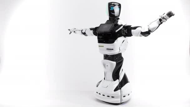 Robotika modern technológia. A világos stúdió robot. Android emeli, és csökkenti a kezek-ra egy fehér háttér. Egy üdvözlő kézzel integetett. Mutatja a gonosz és a jó érzések
