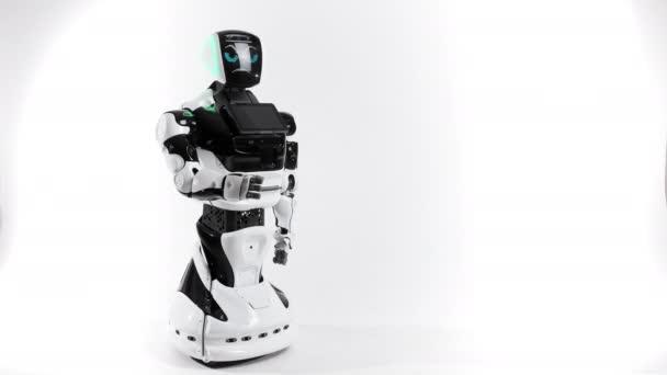 Robotika modern technológia. A világos stúdió robot. Android emeli, és csökkenti a kéz egy fehér háttér. Mutatja a gonosz és a jó érzések. Nézi a kamera