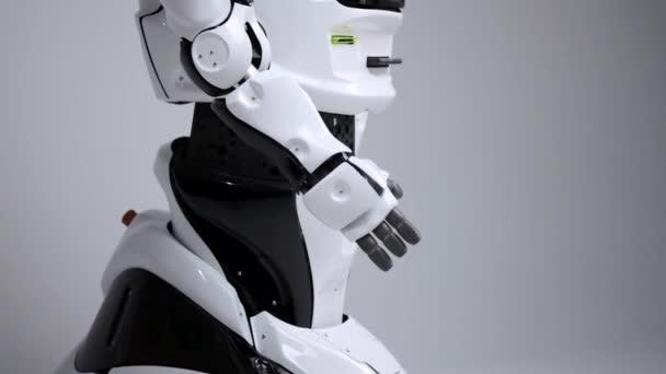 Moderní robotická technologie. Bílá moderní robot v jasné studio. Android se ohýbá jeho ruku, ukazuje jeho klouby. Ukázka z robota na bílém pozadí. Budoucnost