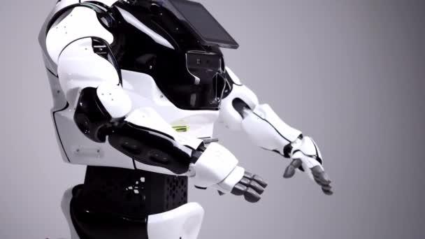 Moderní robotická technologie. Bílá moderní robot v jasné studio. Android, tanec, mávaje rukama. Ukázka z robota na bílém pozadí. Budoucnost.