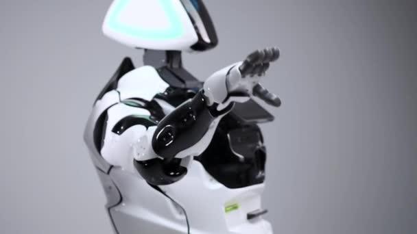 Moderní robotická technologie. Bílá moderní robot v jasné studio. Android a pozdrav rukou, pozdraví diváka. Ukázka z robota na bílém pozadí. Budoucnost.