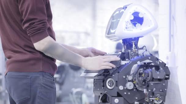 Inženýr upraví robota. Inženýr se zřizuje nový robot. Klepnutí na obrazovce robota. Pracuje s programem.