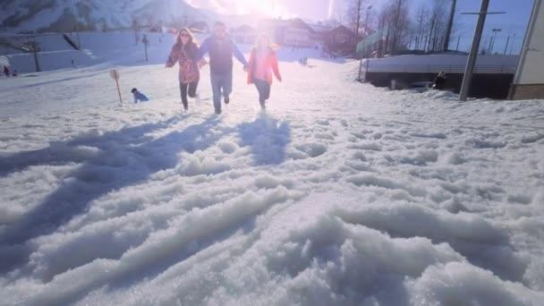 Gesellschaft von Freunden, die Spaß im Urlaub in den Winterbergen haben. Ein Mann und zwei Mädchen genießen den Winter im Skigebiet. Sie rennen im Schnee, springen. Schnee fliegt in die Kamera. hinter dem Berg