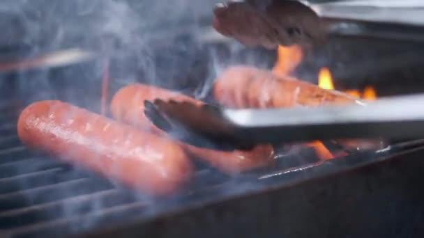 Chutné šťavnaté klobásy grilovacího ohně. Kuchařka připravuje klobásy na gril. Hází gril a převrátí se. Rodinné letní prázdniny.