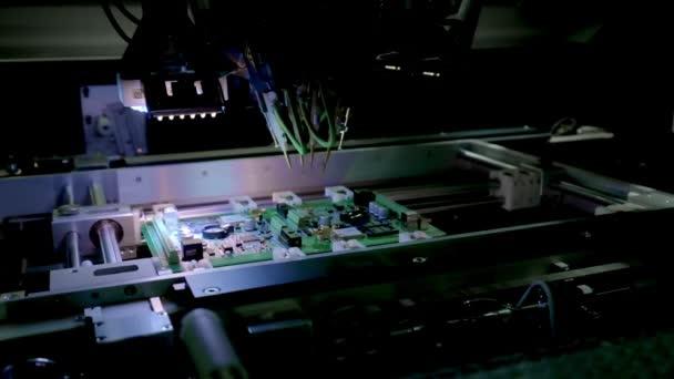 Gyári gép munkahelyi: nyomtatott áramkör being összeszerelve automatizált robot kar, felületre szerelt technológia csatlakoztatása microchips az alaplap. Időközű makró közeli felvételek.