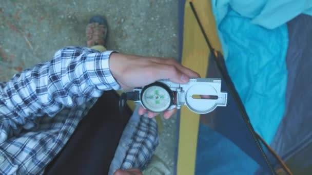 Close up on compass instrument in gloved hand . Mountain hiking trails. Winter mountain trip concept.