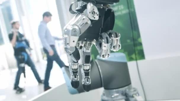 Új technológiák közöttünk. A robotok keze forog és mozog. Összenyomja és unclenches ujjak. Fényes tudományos szakiroda vagy laboratórium.