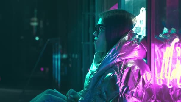 Millennial enigmatic pretty girl near glowing neon wall at night. Mysterious hipster teenager in glasses. Beautiful stylish teen wearing shiny laser jacket and sunglasses. bad lifestyle.