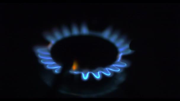 Küchenherd eingeschaltet. Herdplatte entzündet sich in eine blaue Kochflamme. Entzündung des Erdgases aus nächster Nähe.