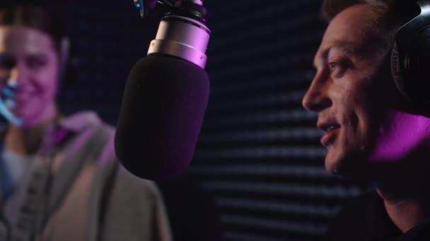Podcast. Zwei gut aussehende junge Männer moderieren einen Podcast über Musik. Ein schönes Mädchen und ein Mann arbeiten in einem professionellen Studio. Das Mädchen interviewt einen Mann. In einem Sendestudio ins Mikrofon sprechen