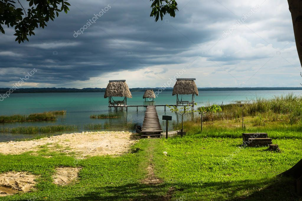 Hammocks on dock along the grass covered lake shore with dark blue cloudscape and sunshine, El Remate, Peten, Guatemala