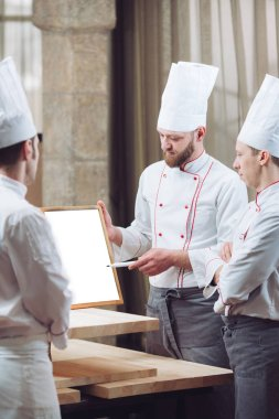 Head Chef and his staff in kitchen. interacting to  in commercial kitchen.
