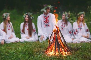Yaz ortası. Yangın yakınındaki ormanda oturan Slav giysili gençler.
