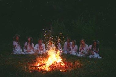 Yaz gecesi. Şenlik ateşi oturan Slav giysili gençler.