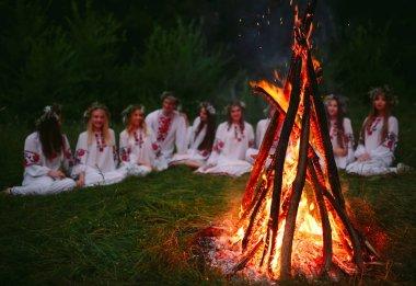 Yaz gecesi. Şenlik ateşi oturan Slav giysili gençler