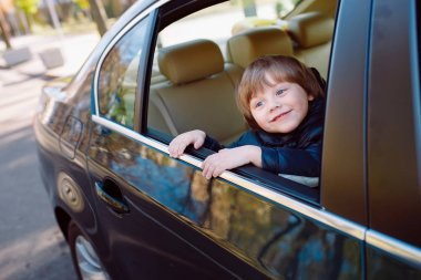 Baby boy in the black car with beige interior.
