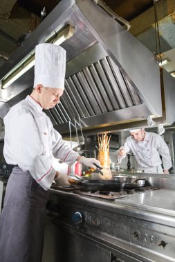 Chef in restaurant kitchen at stove with pan, cooking