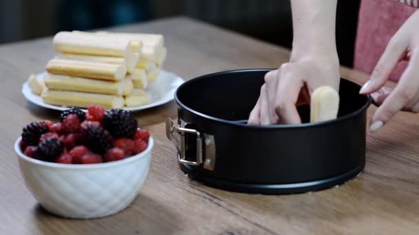 Žena připravuje francouzské charlotte koláč s letním ovocem v domácí kuchyni