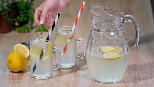 Két befőttesüvegbe pohár házi készítésű limonádét a fából készült háttér
