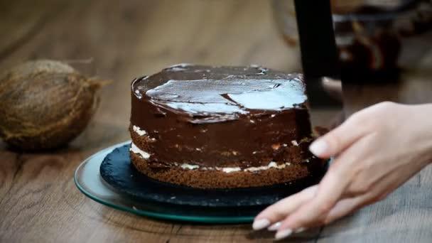 Cukrář, pokrývající dort s čokoládovou smetanou.