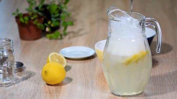 V džbánu citronů nalijte vodu. Sklenice na šumivé vody sodou nápoj limonáda s ledem a vápno plátek citronu na bílém pozadí