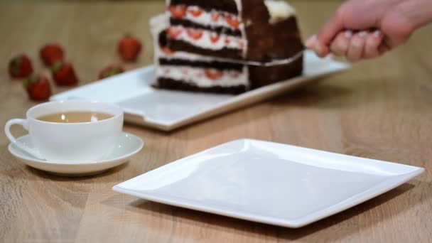 Putting a piece of chocolate cake with fresh strawberries in a plate.