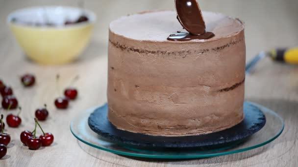 Cukrász csokoládé önti a sütemény.