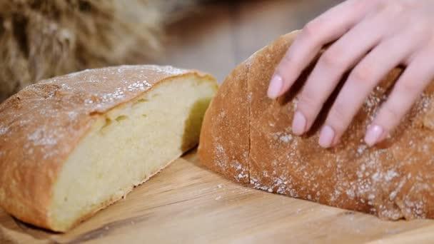 Nő vágás kenyér, fából készült táblán. Pékség. Kenyér előállítása.